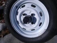 15 x 5.5 stock rims with black center caps and lug covers