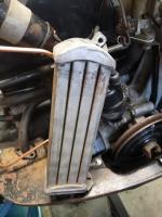 Dome top oil cooler with fan shroud bolt attachment