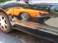 Reflection of Ghia aside modern sedan.